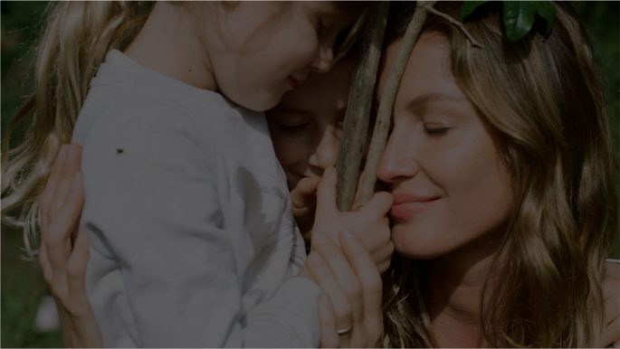 gisele bündchen e suas duas crianças, abraçados, e de olhos fechados. A menina segura alguns gravetos